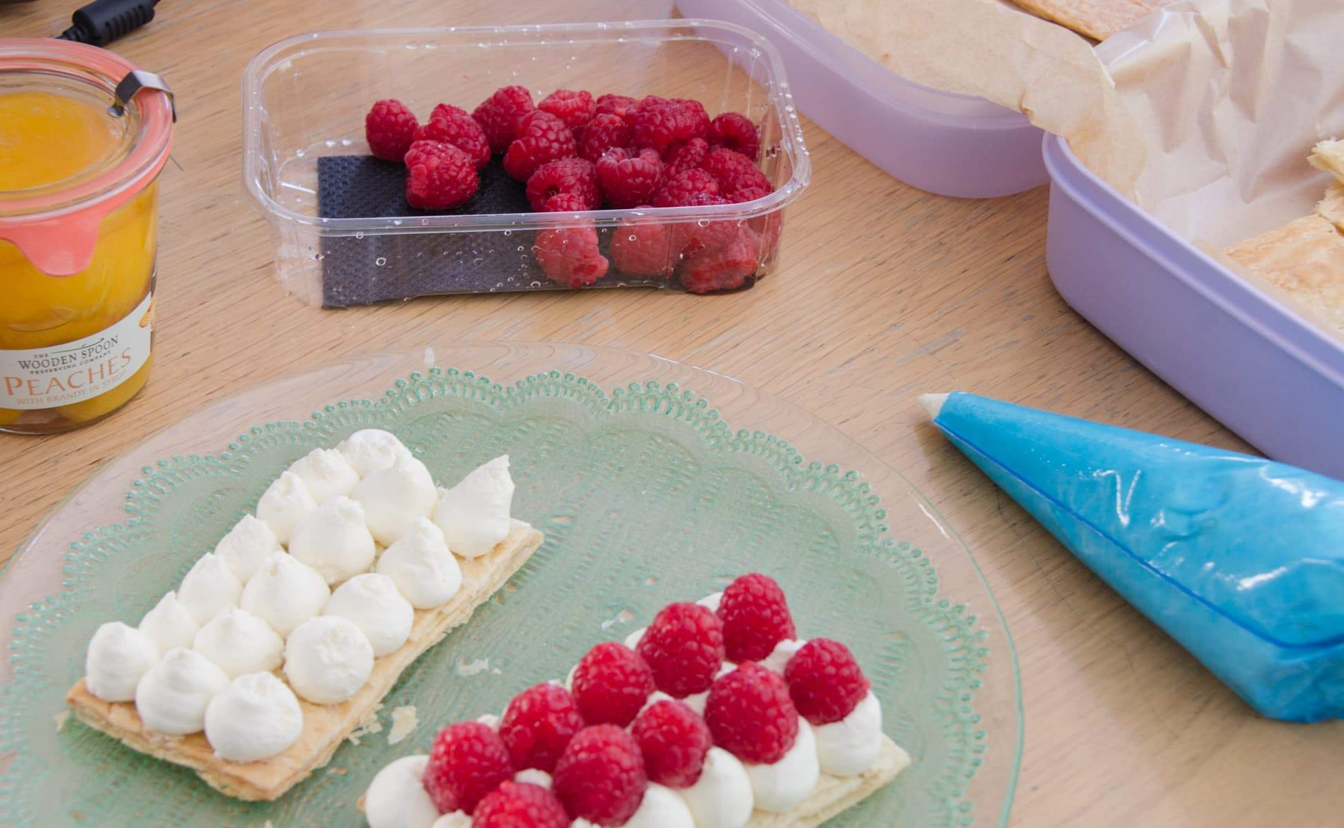 puff pastry slices being layered with cream and raspberries and peaches