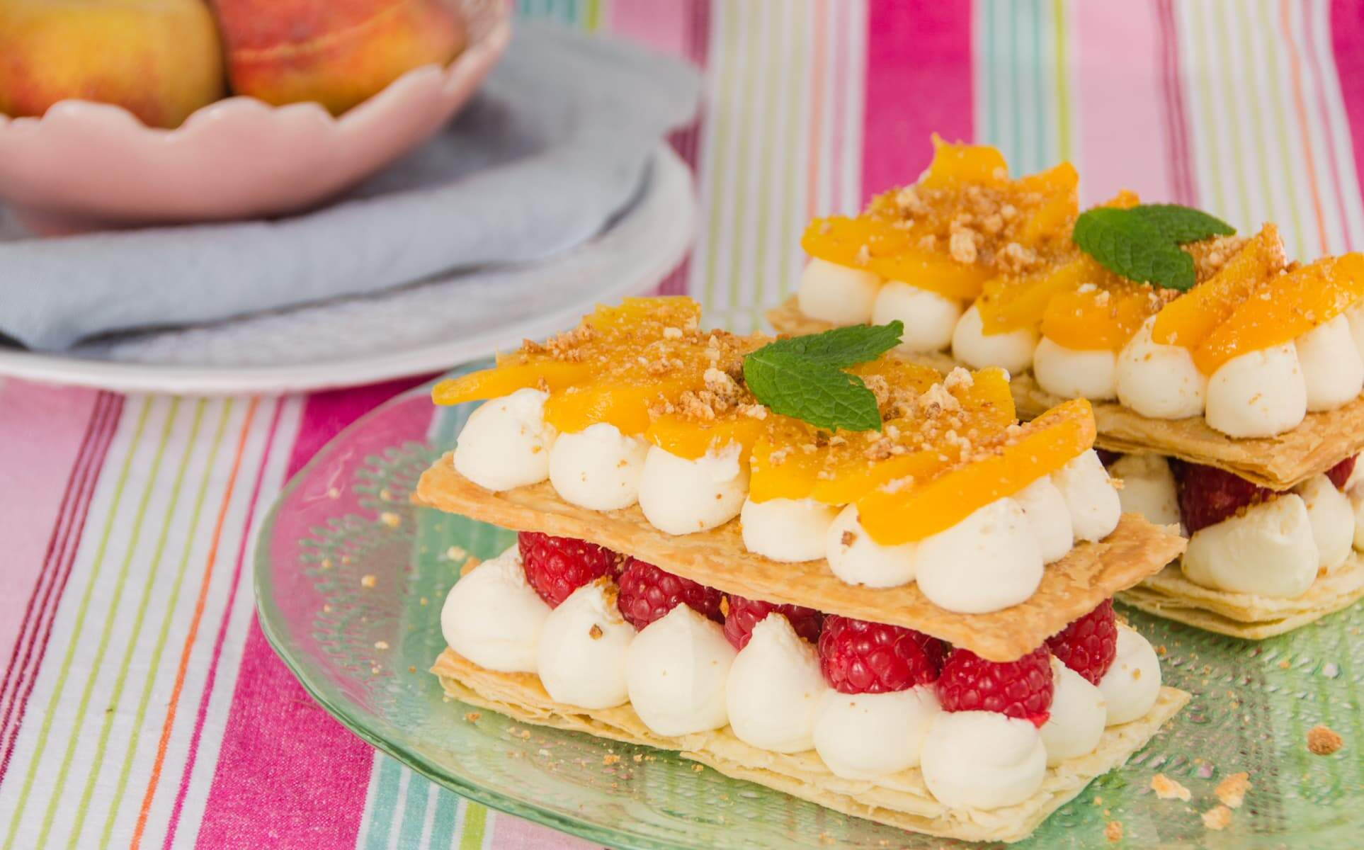 peach & raspberries layered beteen puff pastry slices with cream served outside