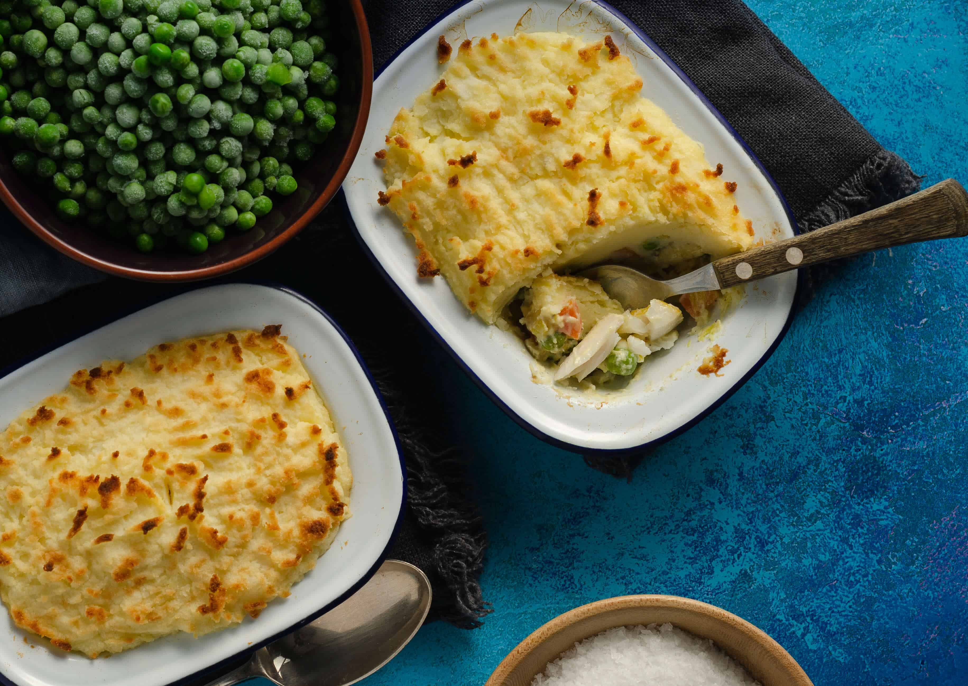 2 portions of fish pie, a blue background, salt and a large bowl of peas, with a spoon dipping into one pie to show the large pieces of fish.