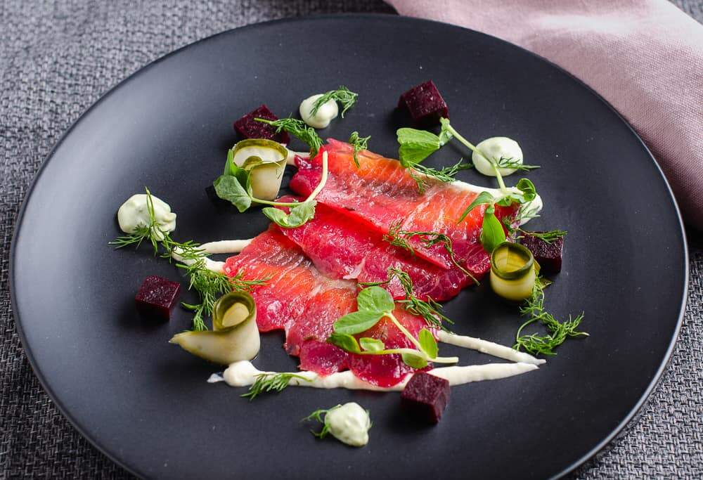 A dish of beetroot cured salmon served on a black plate with a dark grey backgorund, looking down into the plate, also included in the dish, a drizzle of horseradish cream, cubed beetroot, rolled slices of pickled cucumber, an avocado dill cream and then topped with sprigs of fresh dill and pea shoots.