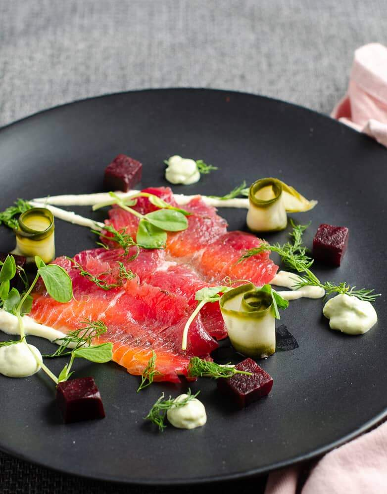 Beetroot cured salmon slices served on a matt black plate on top of a grey backdrop and pink napkin also on the plate are a drizzle of horseradish cream, avocado dill cream, cubed beetroot, rolled slices of pickled cucumber and finished with fresh dill and pea shoots.