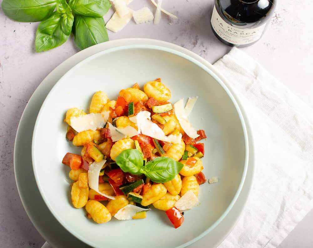 View from the top of a bowl of gnocchi tossed with diced chorizo, fresh tomatoes, diced courgettes and topped with shavings of parmesan and fresh basil with tomatoes and olive oil in the background.