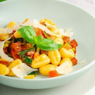 A vertical image of a bowl of gnocchi with fresh tomatoes, chorizo, courgettes and garlic with added shavings of parmesan and basil.