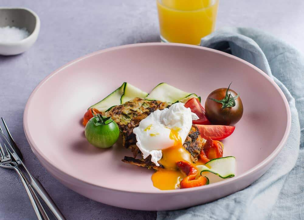 A brunch setting of 2 small gluten free courgette fritters surrounded by fresh tomatoes, slices of courgette and a perfectly poached and runny egg with a glass of orange juice in the back served in a shallow pink bowl and a pale blue napkin to the side and a small pinch pot of salt to the back