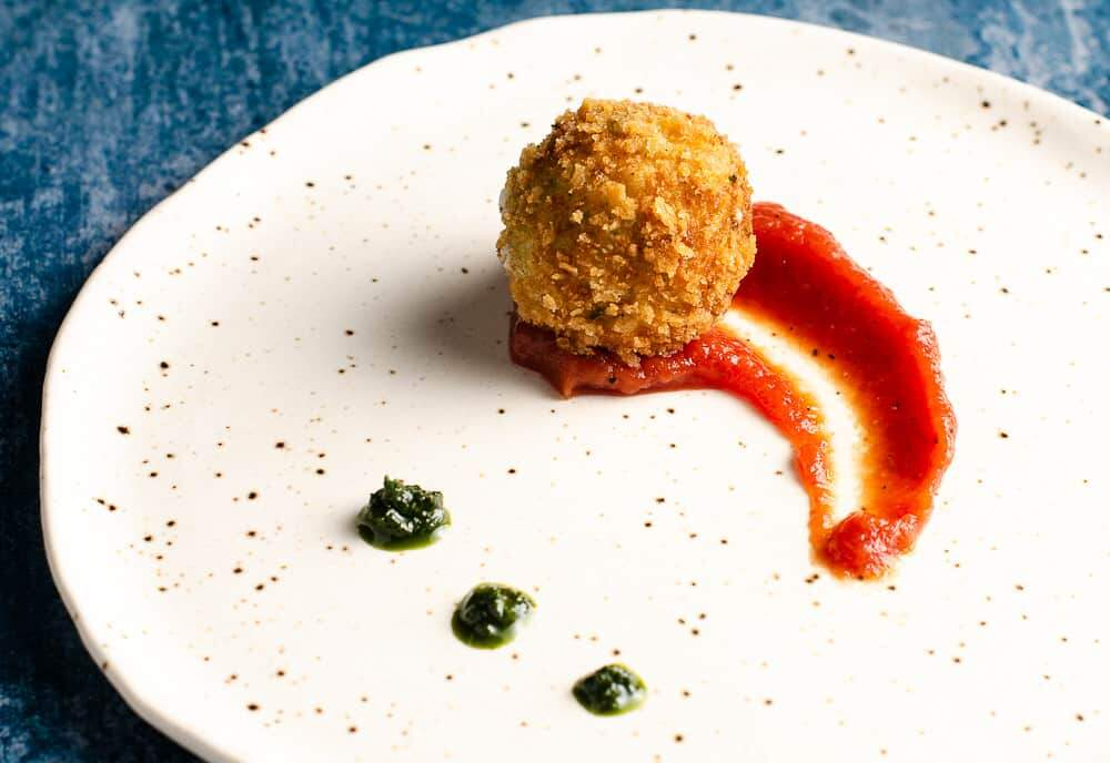 Deep fried potato & cheese ball served on top of a rich tomato sauce with dollops of basil puree on a ceramic plate.