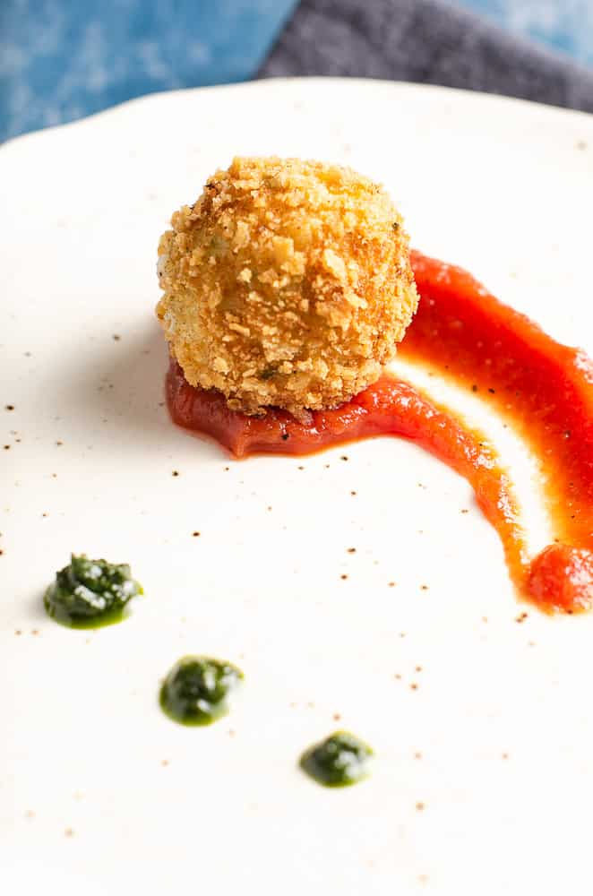 Deep fried potato & cheese ball served on top of a rich tomato sauce with dollops of basil puree on an off white ceramic plate with specs of brown.