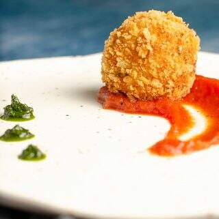 A front close up view of a deep fried potato & cheese ball served on top of a rich tomato sauce with dollops of basil puree on an off white ceramic plate with specs of brown.