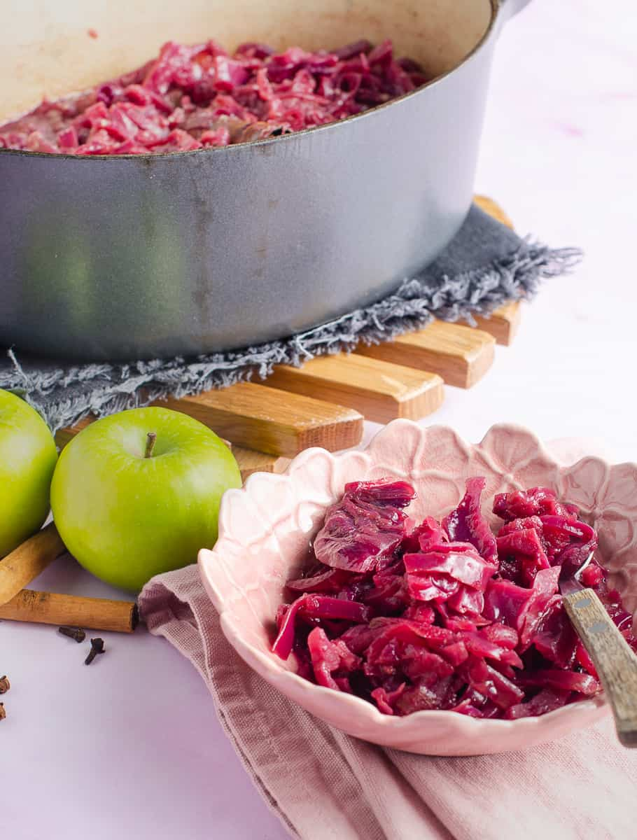 A small pink bowl of braised red cabbage, some green apples, cinnamon sticks and cloves on a pink napkin and a grey casserole to the back of the remainder of the dish.