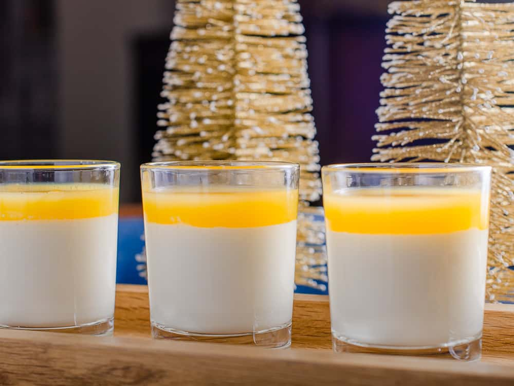 A long wooden serving tray with small individual shot glasses filled with vanilla panna cotta and topped with clementine jeely, with gold Christmas Trees and Golf lights decorating.