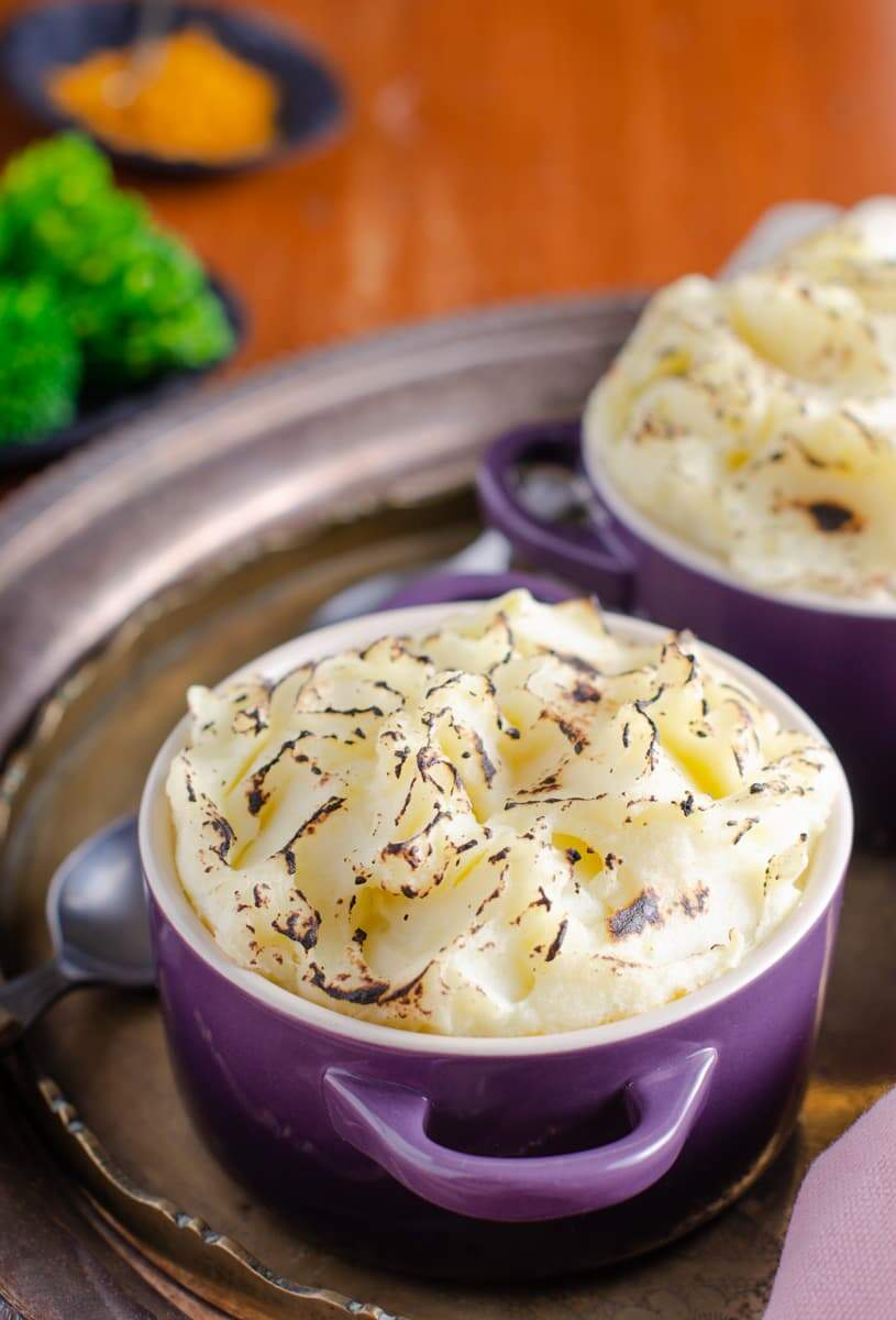 Indian spiced cottage pie topped with grilled mashed potatoes in a purple ceramic dish and another towards the back on a tarnished surface