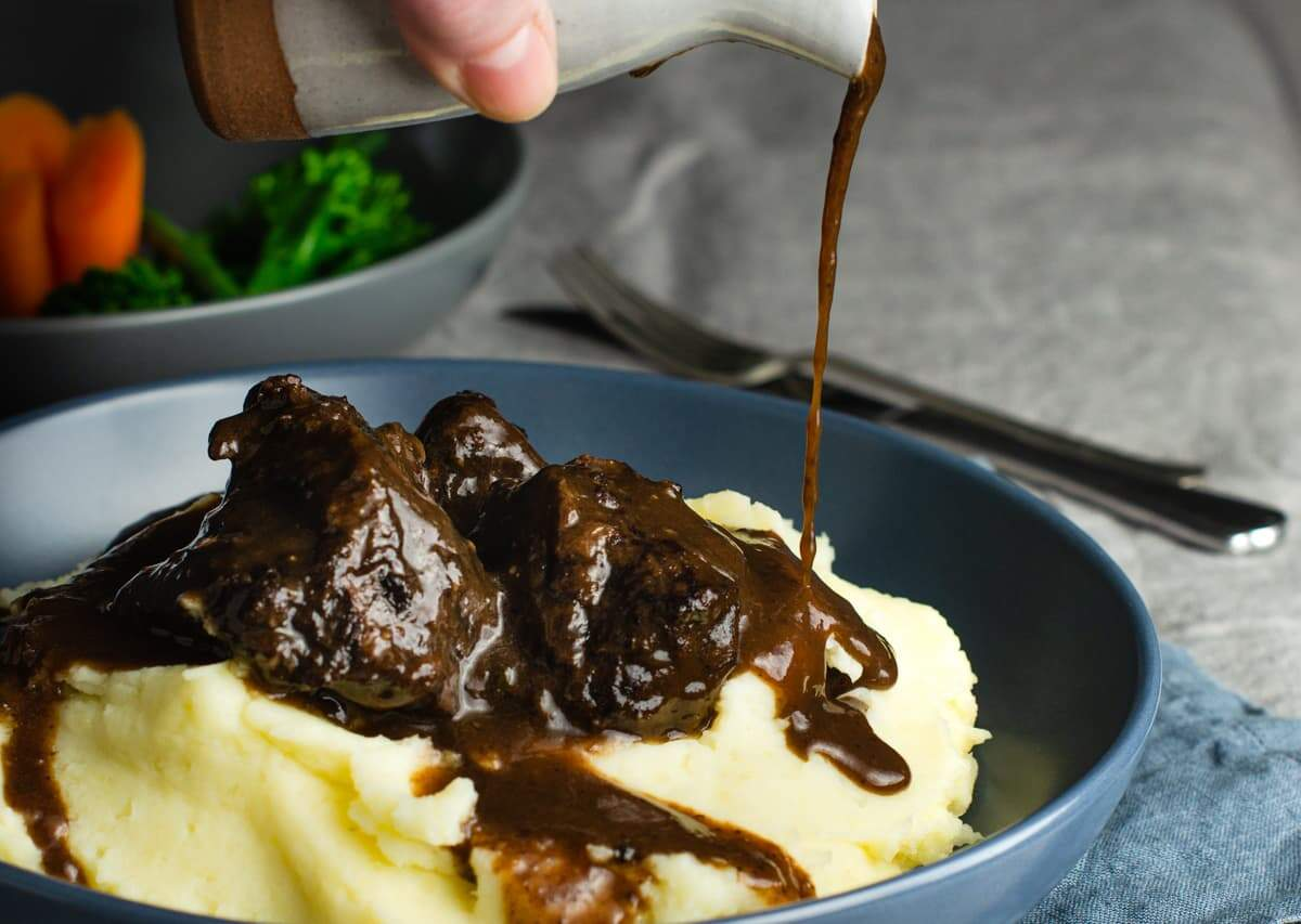 A blue bowl of buttery mashed potato topped with slow braised beef cheeks and gravy being poured over the top sitting on top of a table with a grey linen tablcloth and vegetables to the abck