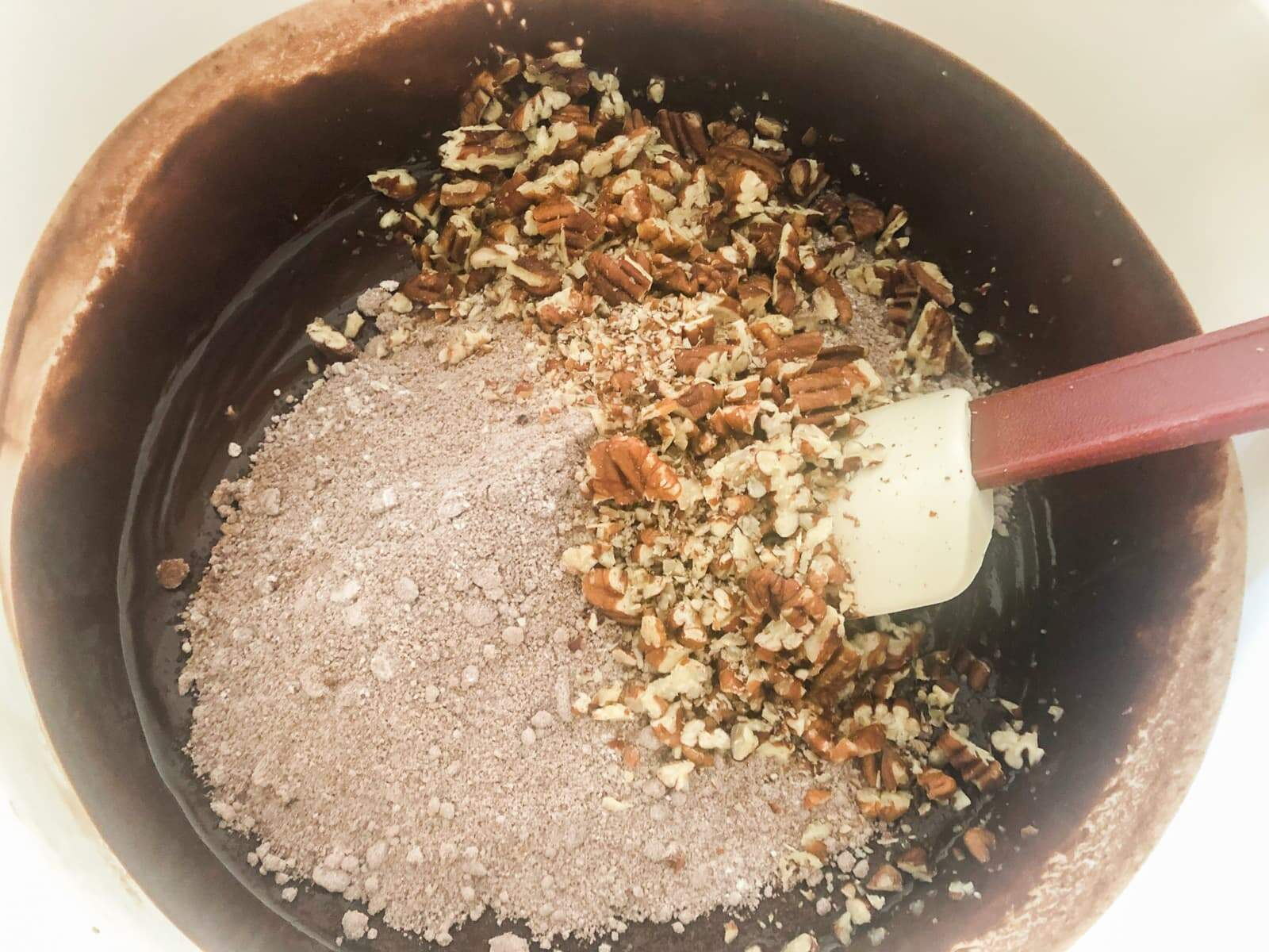W white plastic bowl with melted chocolate and butter and flour, cocoa powder and chopped hazelnuts being added and a spatula ready to mix to make brownies.