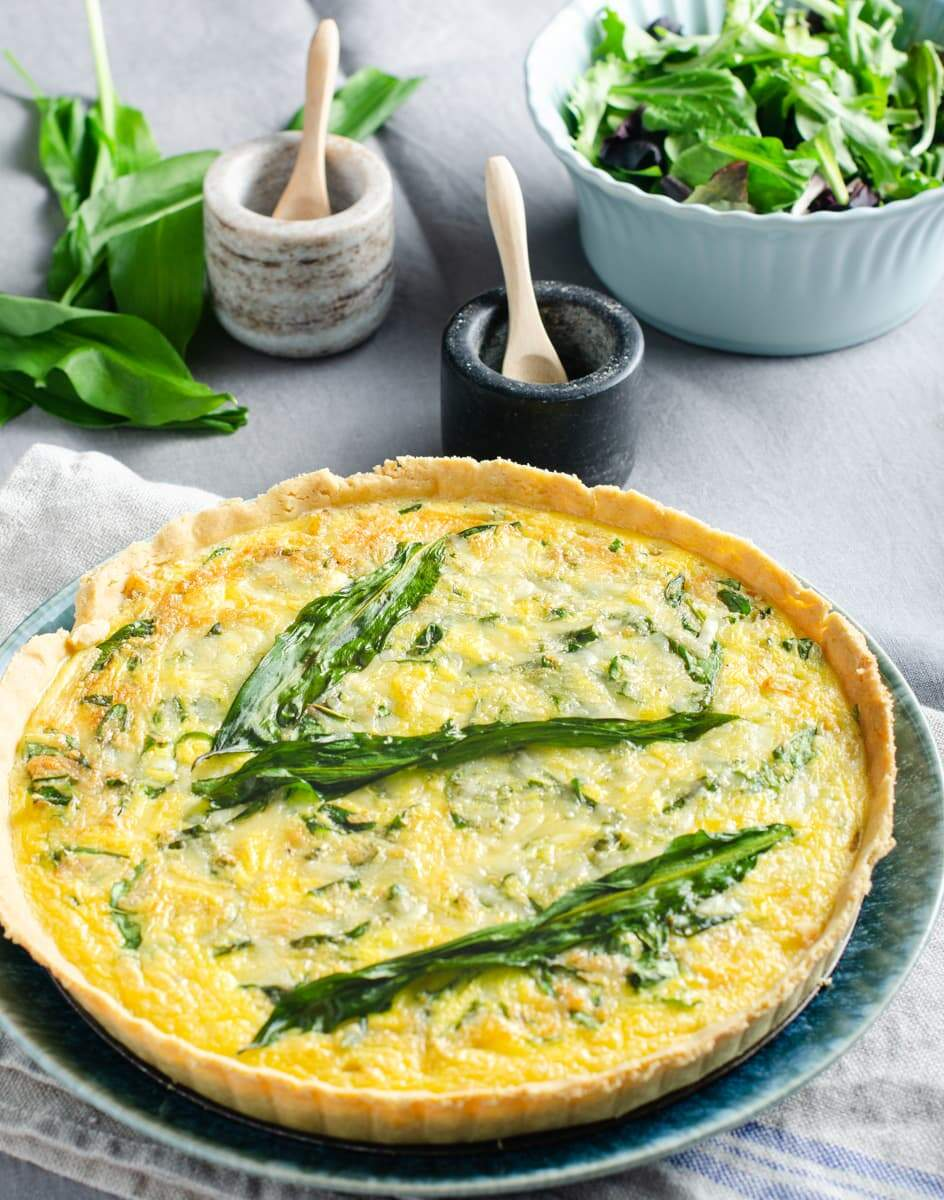 A wild garlic, cheese and onion quiche on a blue plate with fresh wild garlic leaves, a green salad and salt and pepper pots to the back.