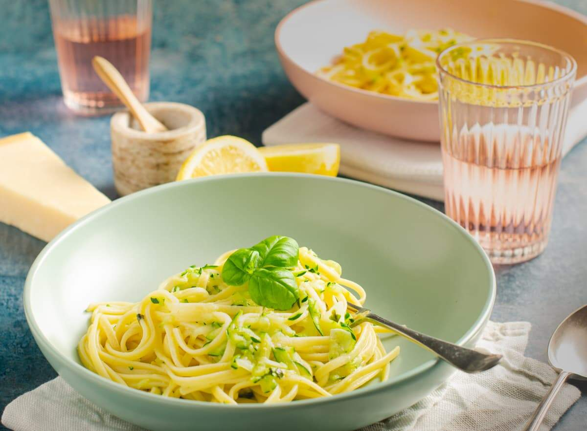 Courgette linguine with lemon and basil in a pale green bowl.