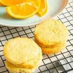 Orange butter cookies on a cooling rack and a sliced orange.