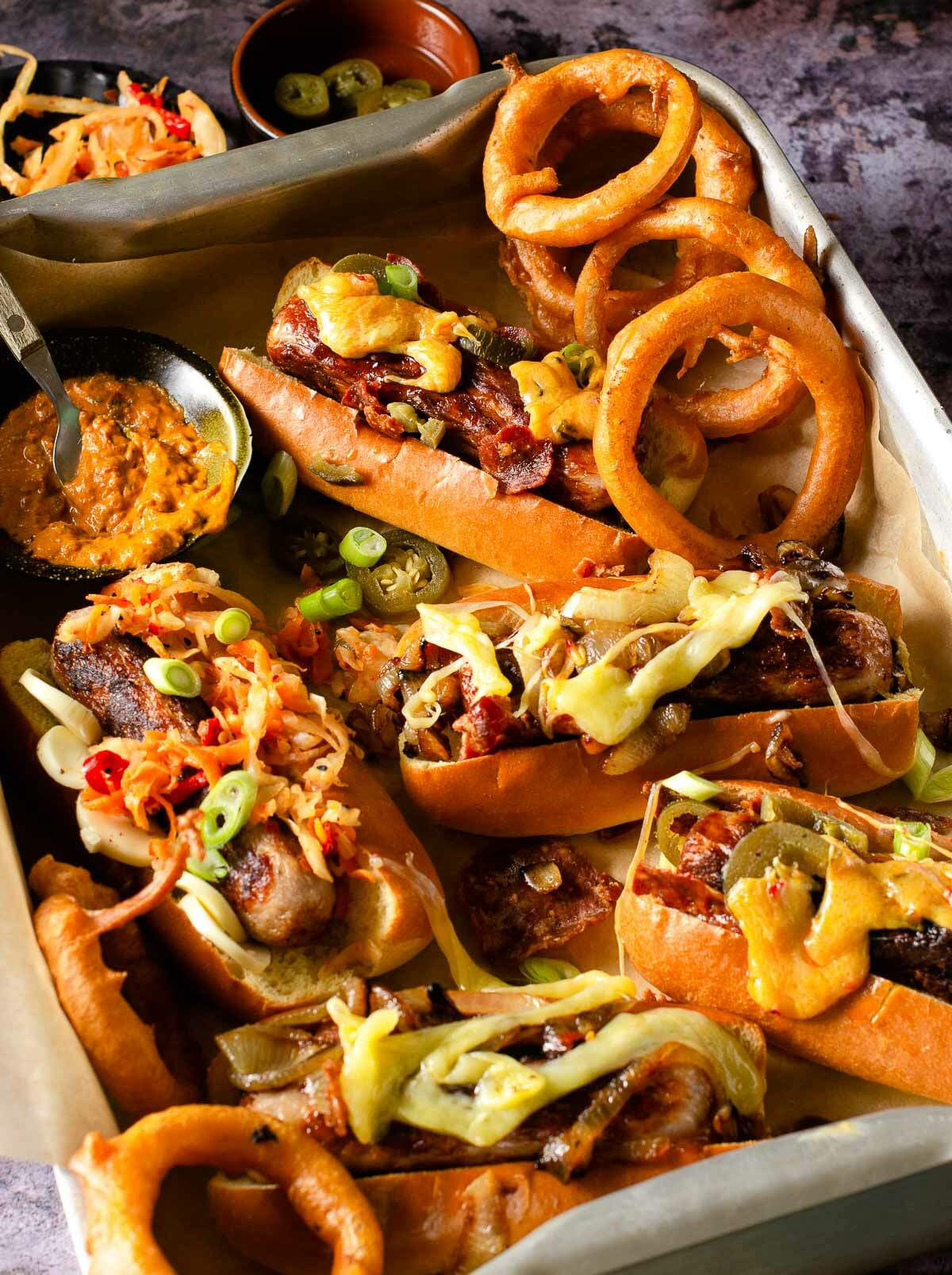 Hot dogs, loaded with toppings in a metal tray.